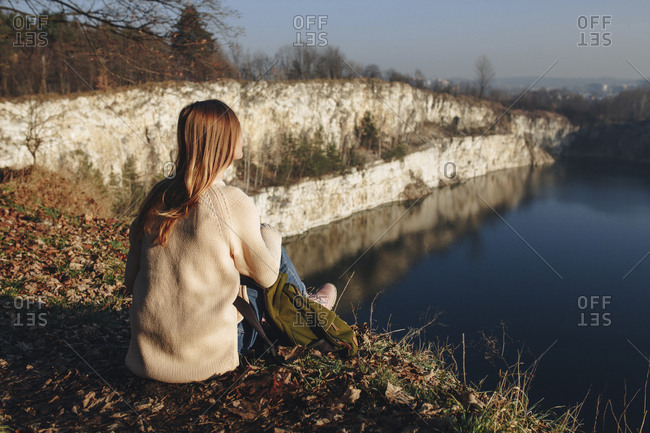 Caucasian woman sitting at the edge of reservoir