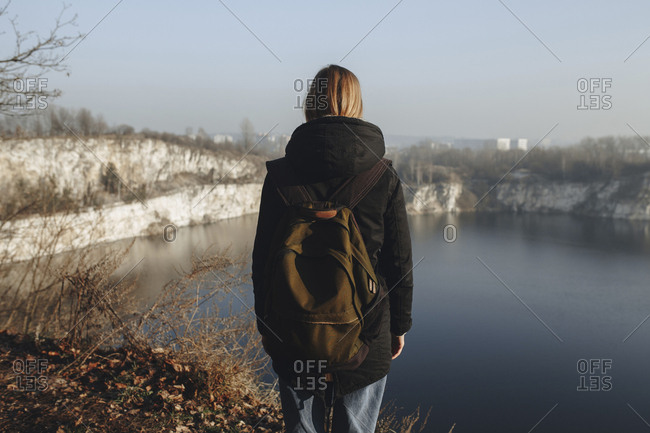 Caucasian woman standing at the edge of reservoir wearing backpack