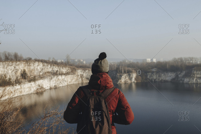 Caucasian man at the edge of reservoir wearing backpack
