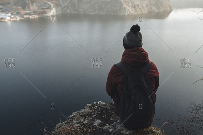 Caucasian man sitting at the edge of reservoir wearing backpack