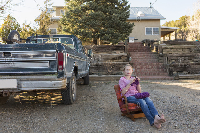 Caucasian girl sitting on chair near truck and knitting