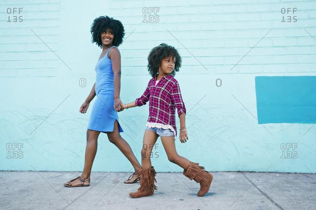 Smiling mother and daughter walking on sidewalk