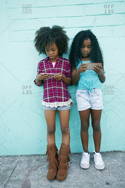 Girls leaning on wall texting on cell phones