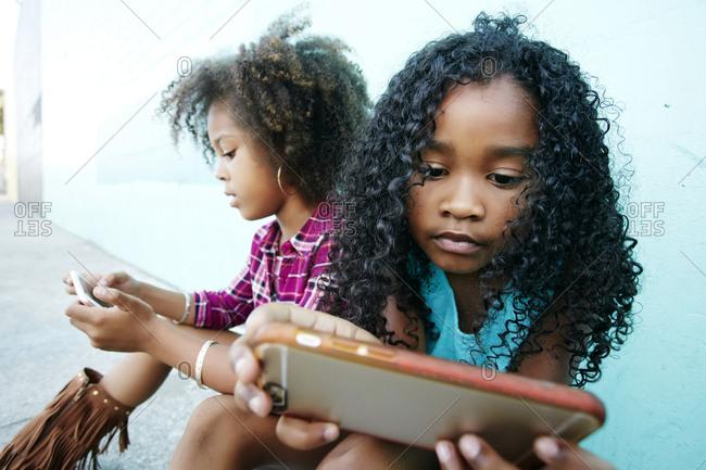 Girls sitting on sidewalk texting on cell phones