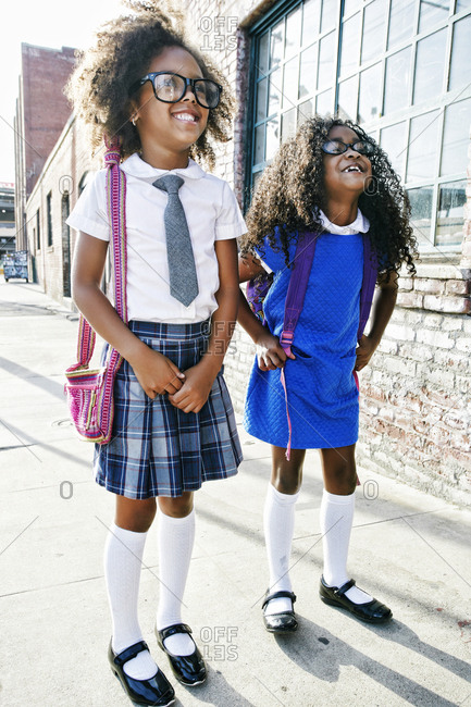 Smiling girls standing on sidewalk ready for school