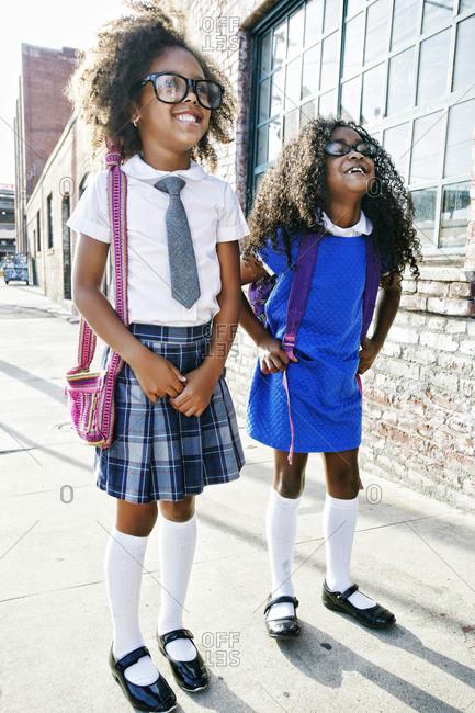 Smiling girls standing on sidewalk ready for school