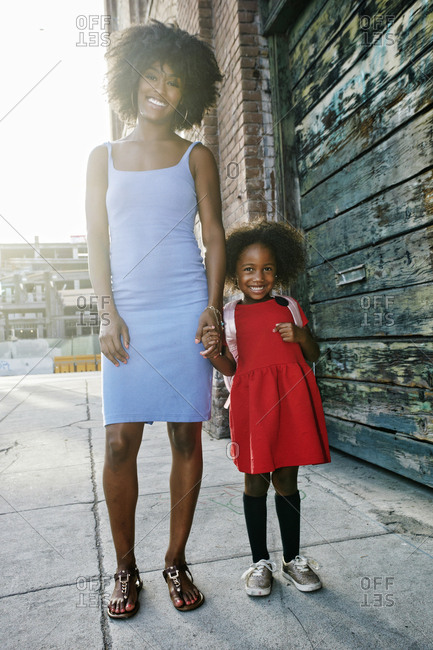 Portrait of smiling mother and daughter standing on sidewalk