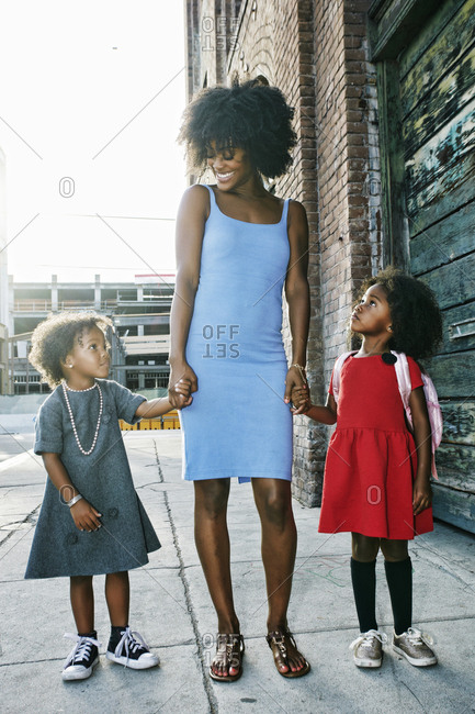 Smiling mother and daughters standing on sidewalk