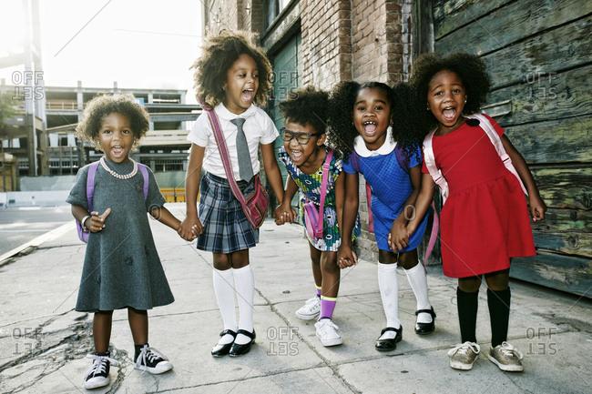 Portrait of girls laughing on sidewalk