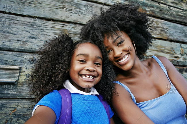 Portrait of smiling Black mother and daughter near wooden wall