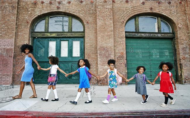 Woman leading girls holding hands on city sidewalk