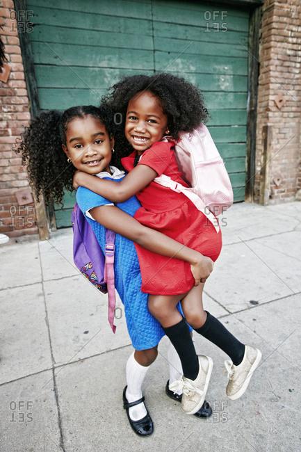 Portrait of smiling girl lifting friend on sidewalk