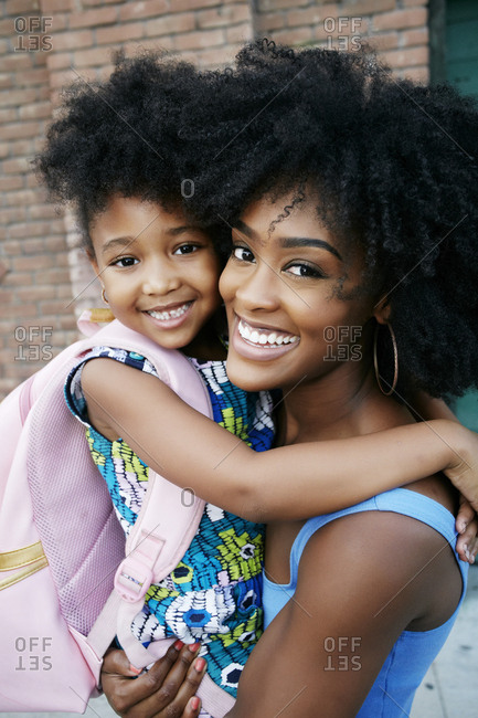 Portrait of Black mother carrying daughter