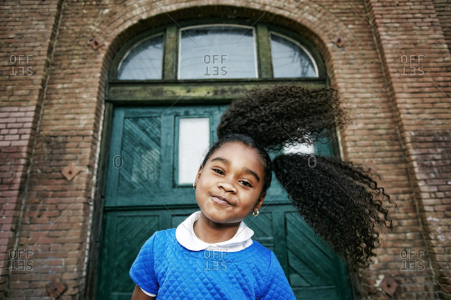 Smiling Black girl tossing hair