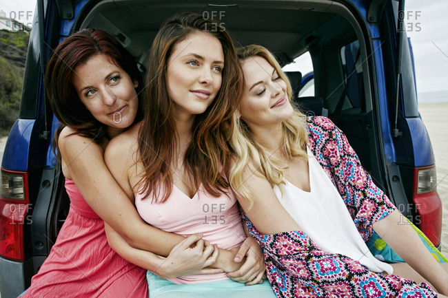 Portrait of Caucasian women relaxing and hugging in hatch of car
