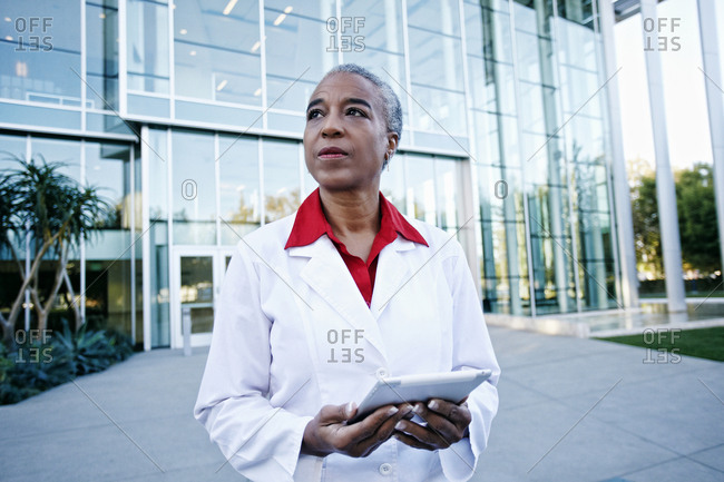 Portrait of serious African American doctor holding digital tablet outdoors