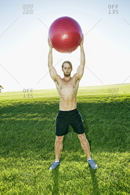Caucasian man exercising with fitness ball in field