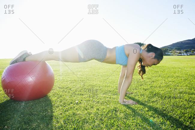Mixed Race woman balancing on fitness ball doing push-ups