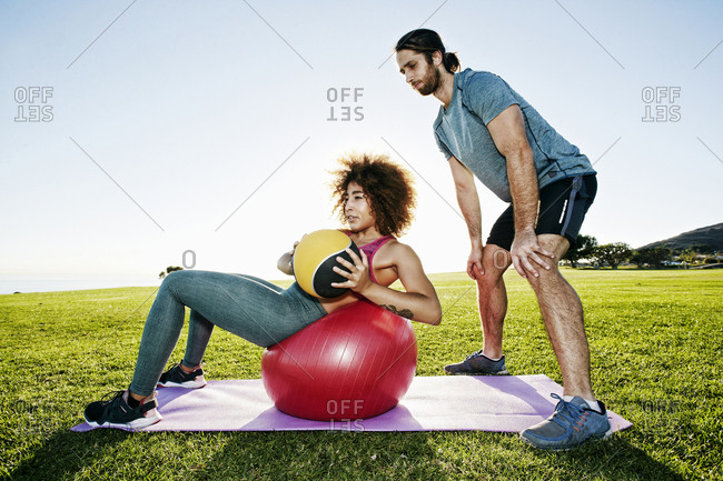 Couple exercising with fitness ball and heavy ball in sunny field