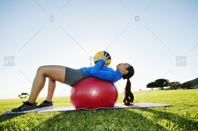 Mixed Race woman exercising with fitness ball and heavy ball in sunny field