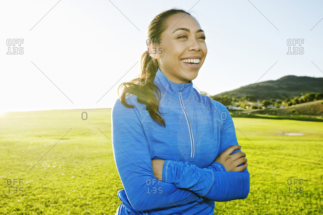 Mixed Race woman laughing in sunny field