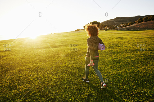 Hispanic woman carrying exercise mat in sunny field