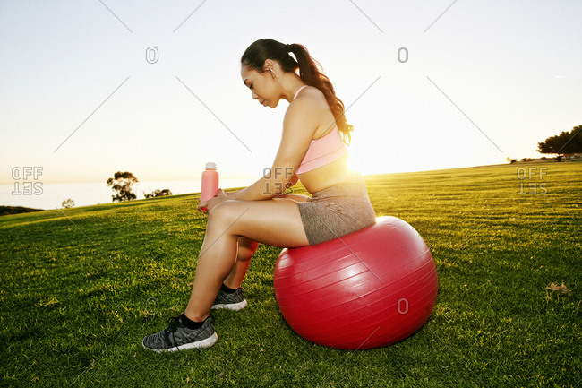 Mixed Race woman resting on fitness ball in sunny field