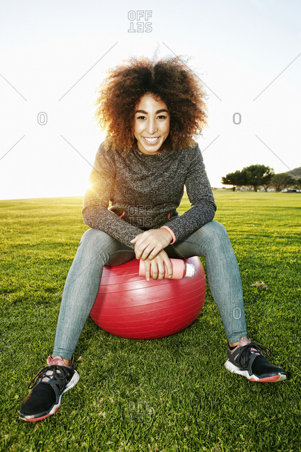 Smiling Hispanic woman resting on fitness ball in sunny field