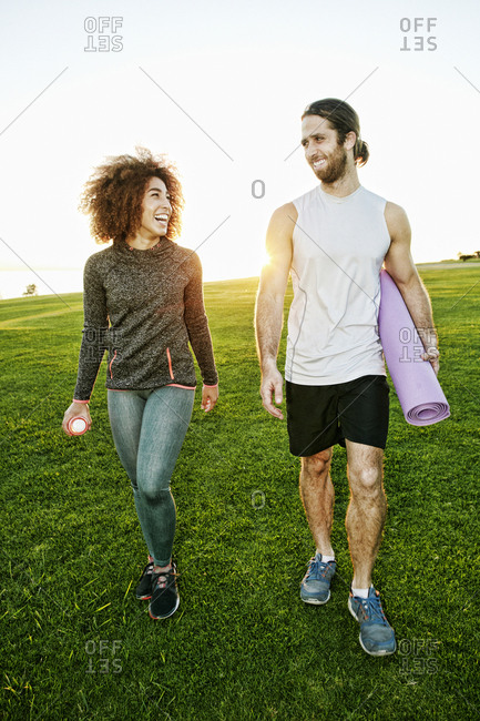 Couple walking in sunny field carrying exercise mat