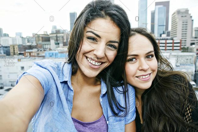 Smiling Hispanic women posing on urban rooftop