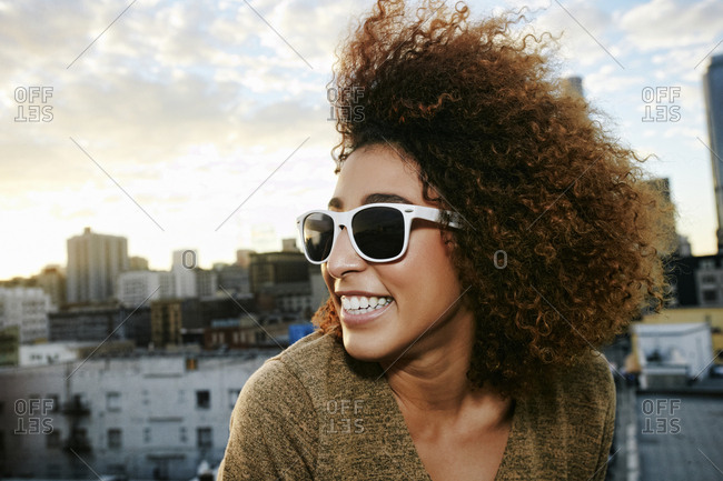 Portrait of smiling Hispanic woman on urban rooftop at sunset