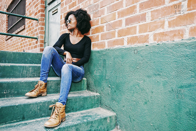Black woman sitting on staircase outdoors