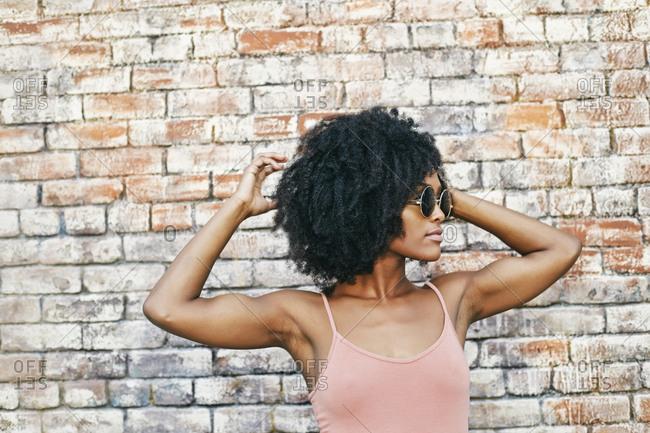 Serious Black woman near brick wall