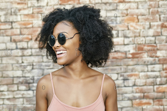 Smiling Black woman near brick wall