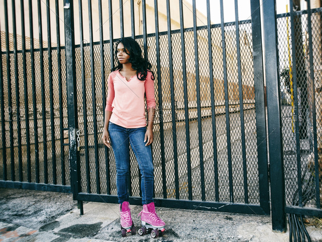 Black woman wearing roller skates near metal gate