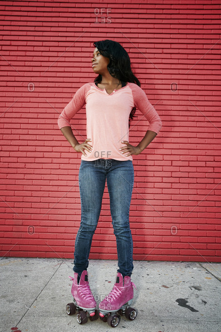 Black woman wearing roller skates on sidewalk
