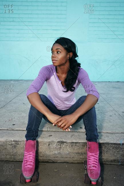 Black woman wearing roller skates sitting on curb