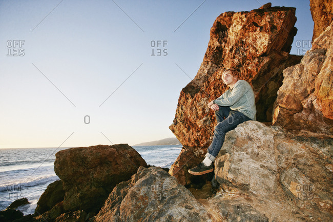 Caucasian man sitting on rock formation at beach