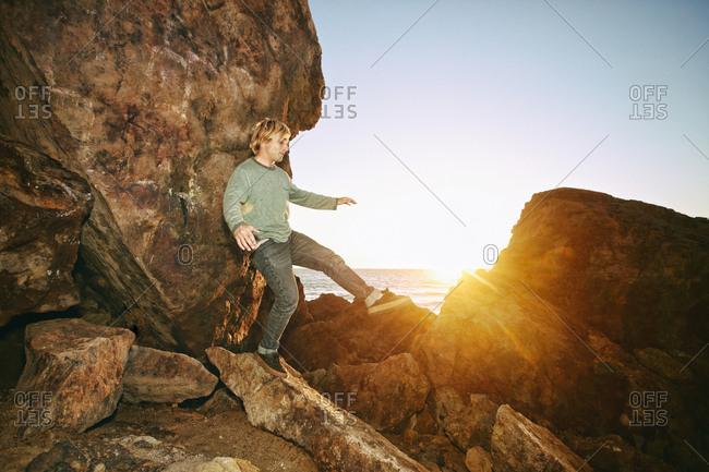 Caucasian man balancing on rocks at ocean
