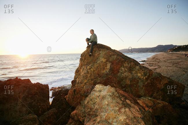 Caucasian man sitting on rock formation near ocean