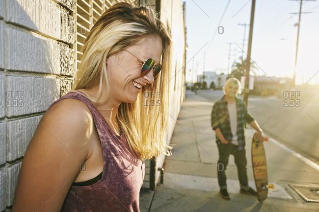 Caucasian woman laughing on sidewalk