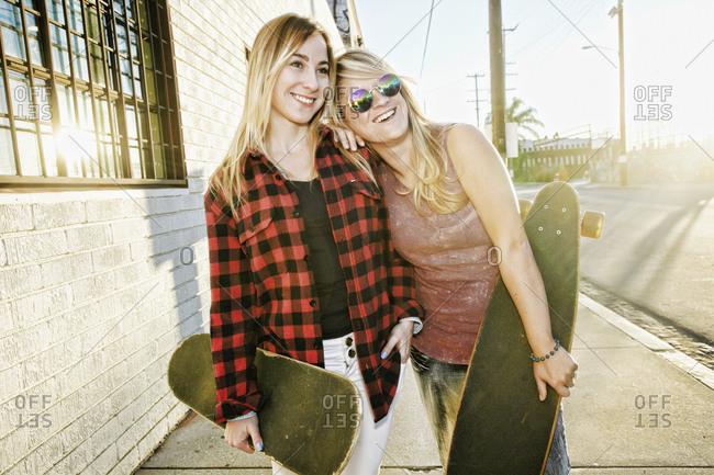 Smiling Caucasian women holding skateboards on sidewalk
