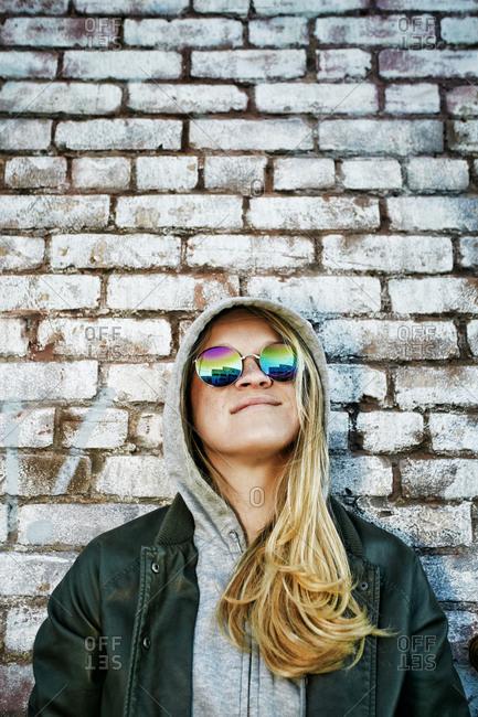 Caucasian woman wearing sunglasses near brick wall
