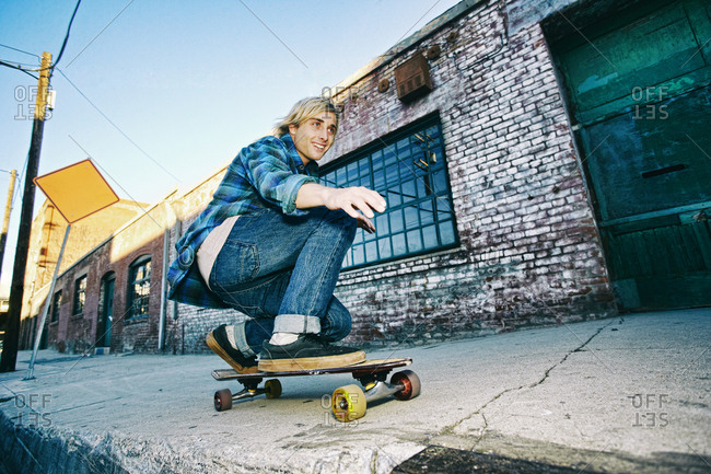 Caucasian man skateboarding on urban sidewalk