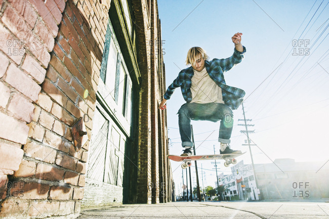 Caucasian man jumping on skateboard on urban sidewalk