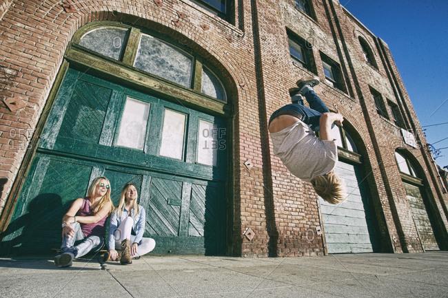 Woman watching man skateboarding on urban sidewalk