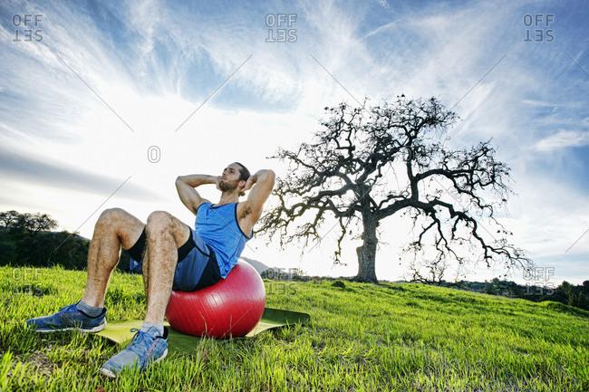 Caucasian man doing sit-ups on fitness ball in field near tree