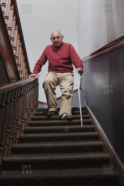 Hispanic man with cane descending staircase