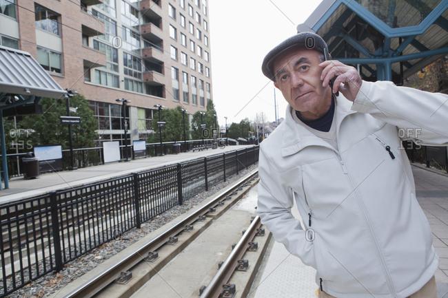 Hispanic man waiting at train station talking on cell phone