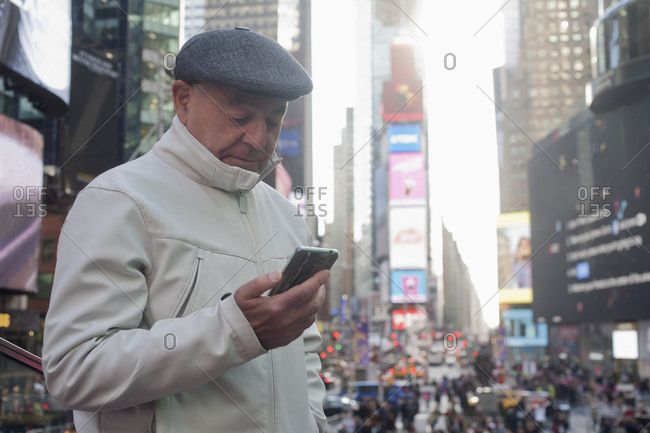 Hispanic man texting on cell phone in crowded city